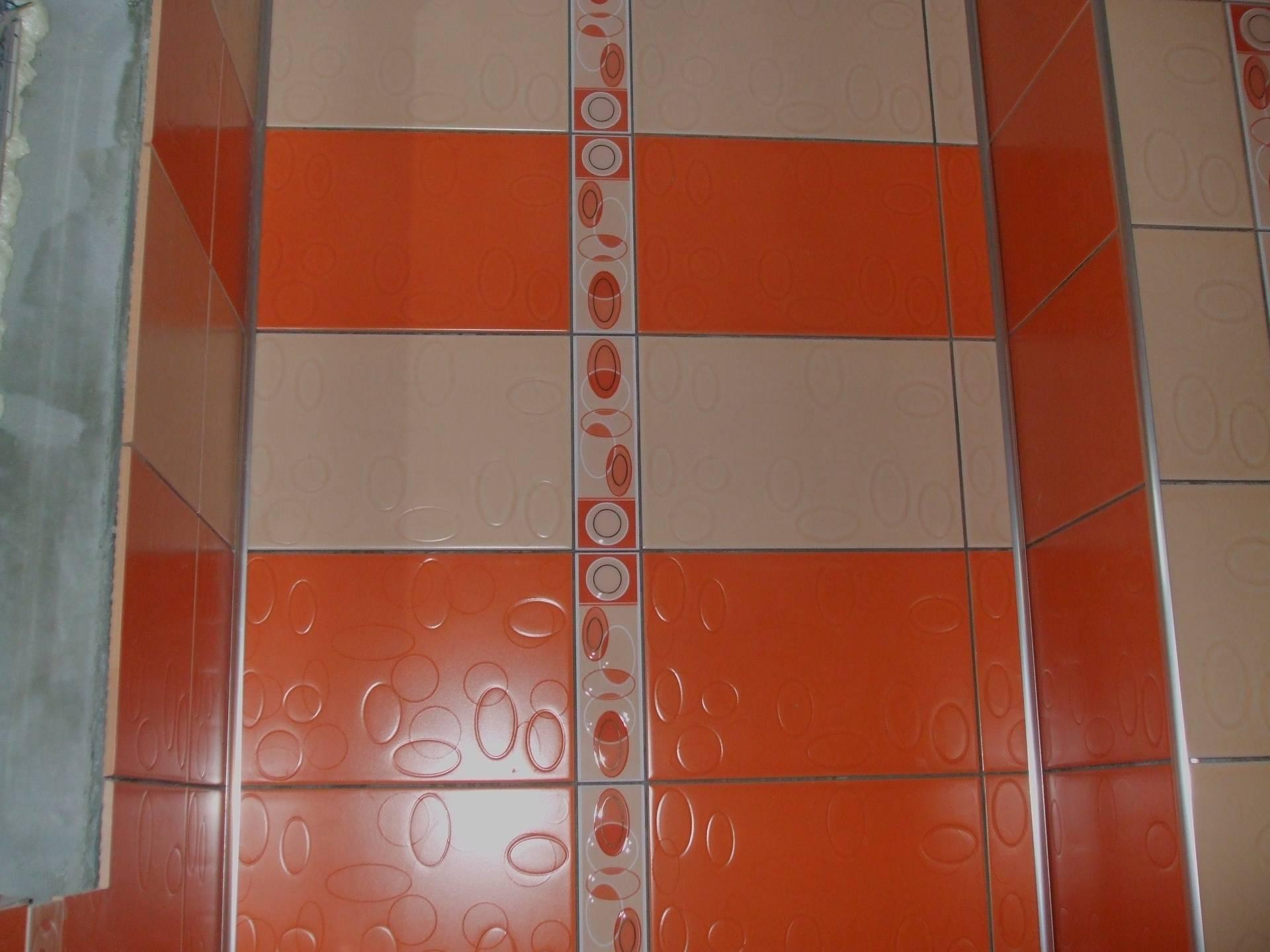 faianta baie orange si crem fasi verticale delimitate de brau faianta cu aspect floral