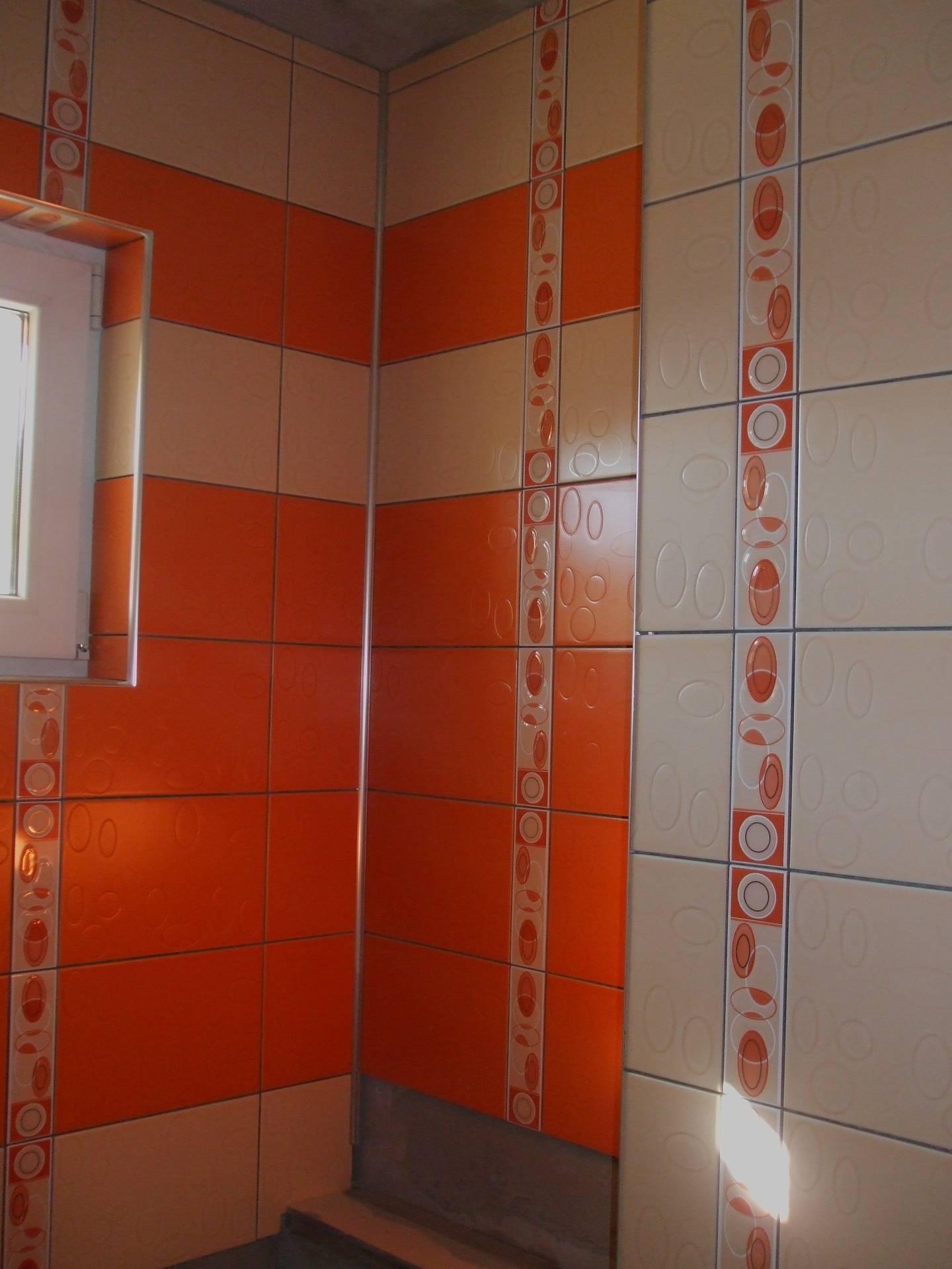 Baie cu faianta portocalie si crem delimitate de brau faianta,design placare faianta fasii orizontale