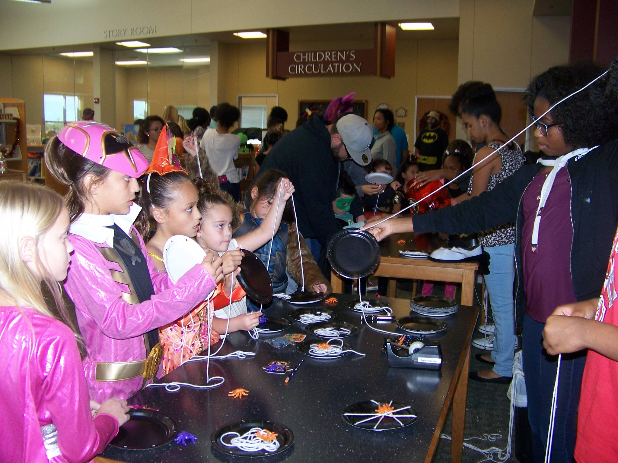 Builders club member helping kids with their Halloween crafts