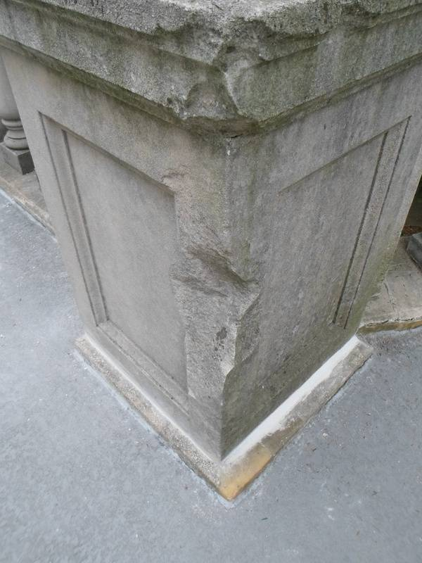 Limestone column with significant damage.