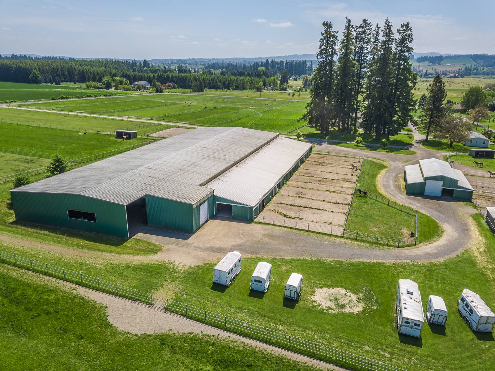 Aerial Arena barn, little barn, trailer parking, runs pastures