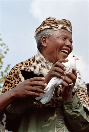 Mandela in traditional clothes with a dove