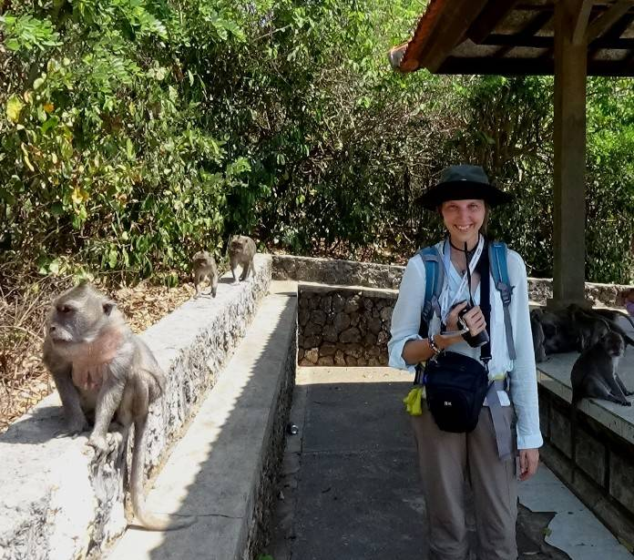 """Anna Holzner (with her hat """"safely"""" jammed down on her forehead) surrounded by the Uluwatu monkeys (October 2015)"""