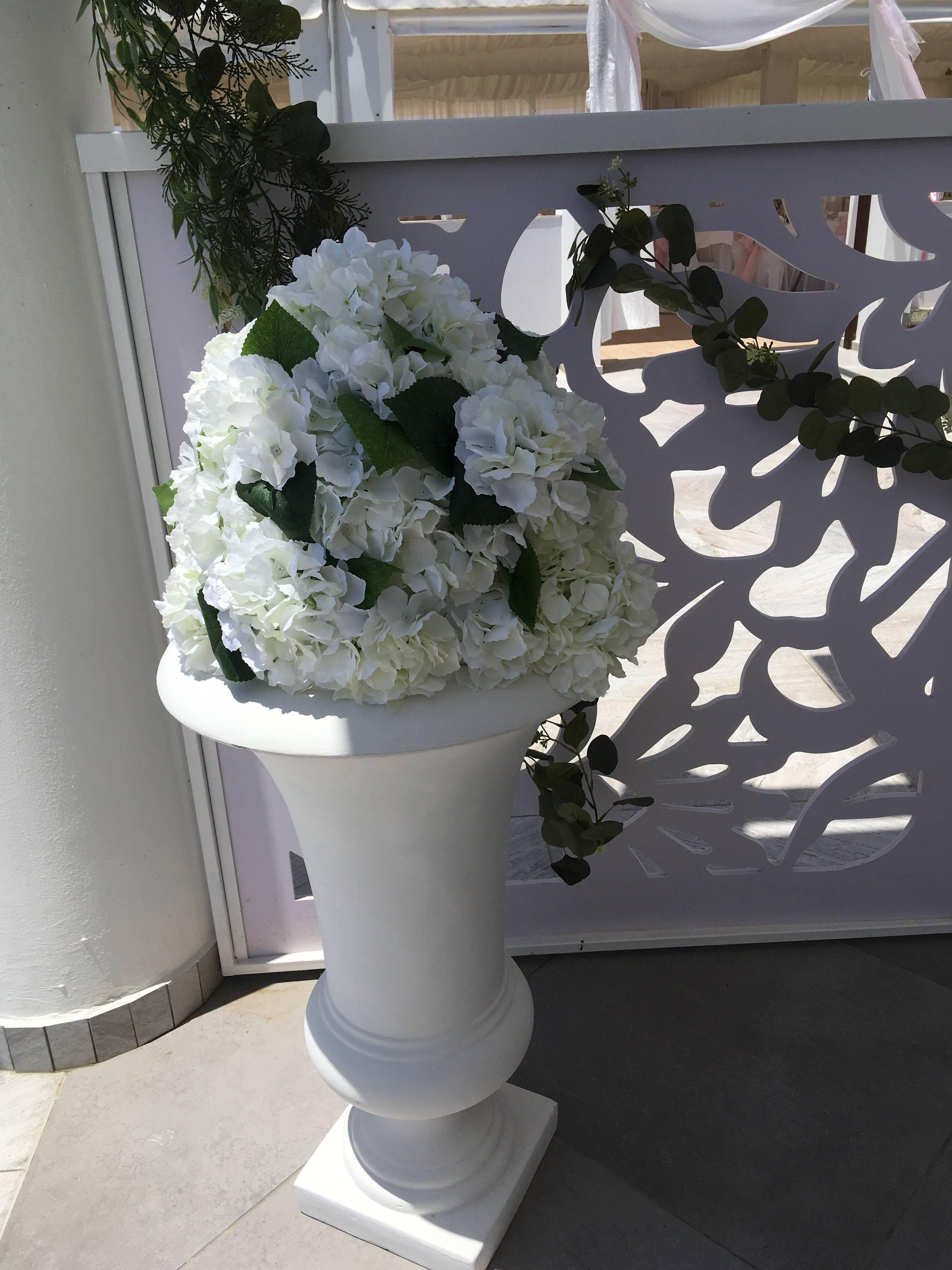 Hydrangea arrangements in white urns.