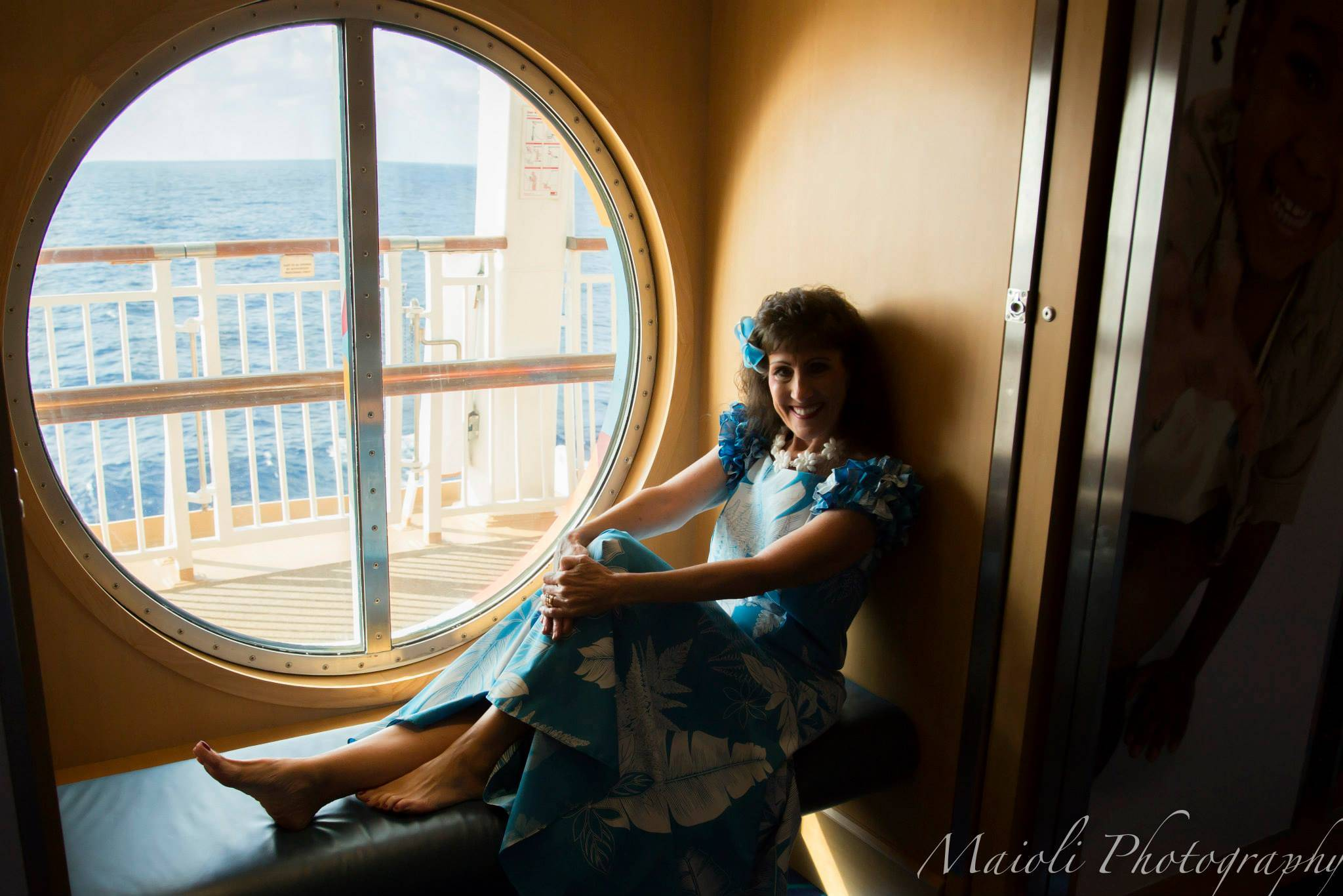 Violet Ray seated in port hole window on the Norwegian Dawn
