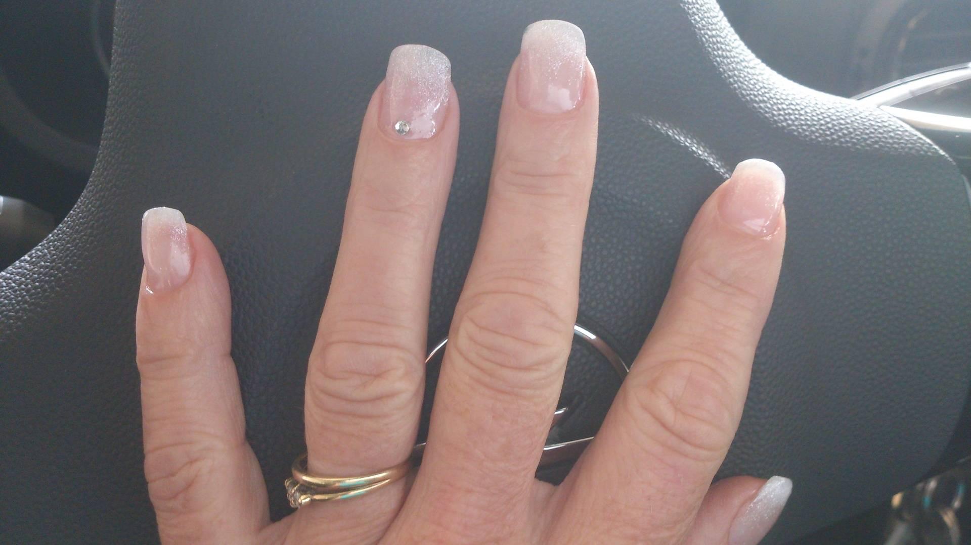 acrylnagels met een witte glitterfading en strasssteentje