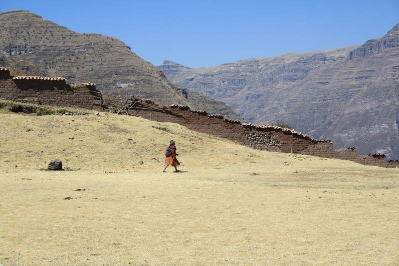 An Andean woman walking through the school yard.