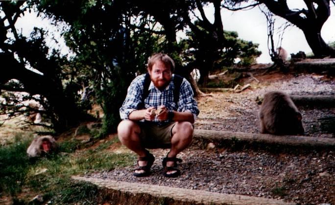 JB Leca, surrounded by two Japanese macaques, and engaging in stone handling behavior at Arashiyama, Kyoto, Japan (June 2004)