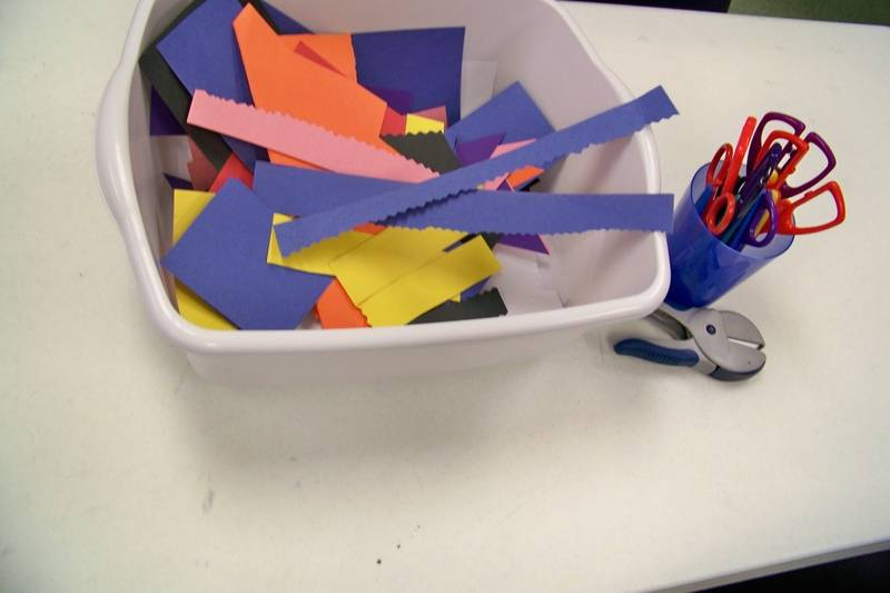 Paper scraps, cropping scissors, hole punches