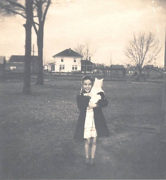Judi Raburn in McCoy Ainsleys front yard with cat Spot. 1940s. Ponzer post office and Manning house in background.