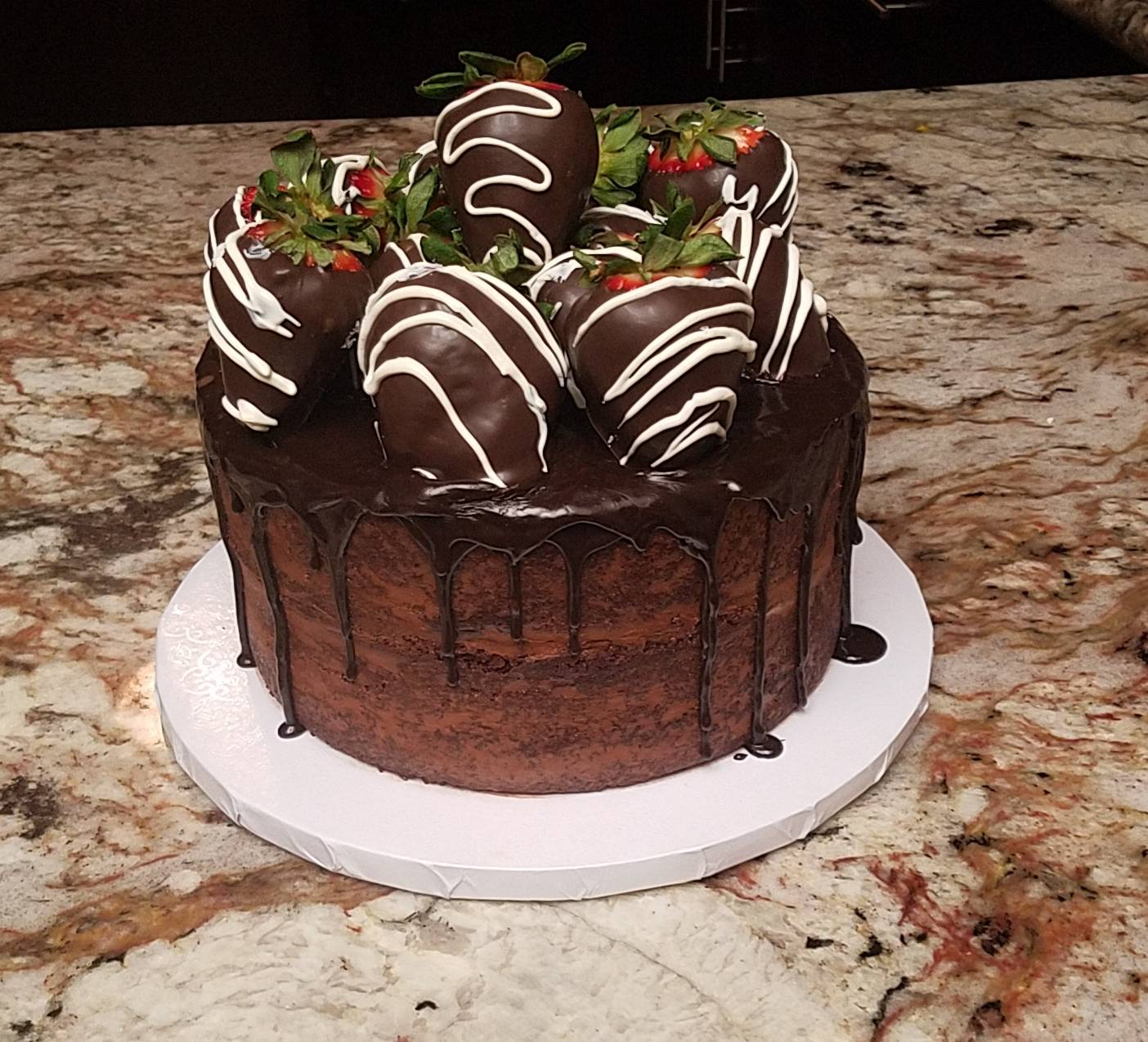Naked Chocolate Drip Cake with Chocolate Covered Strawberries on Top