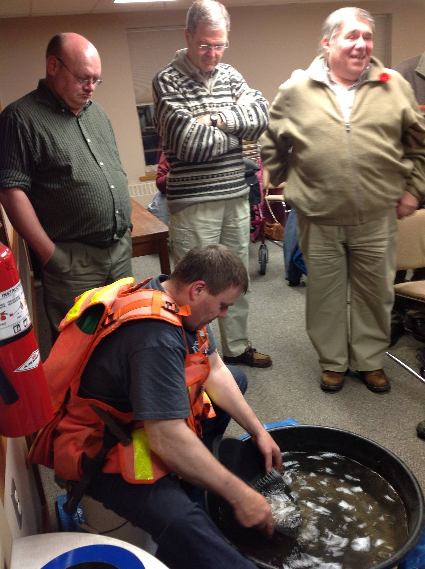Members look on as gold panning is demonstrated in a small tub