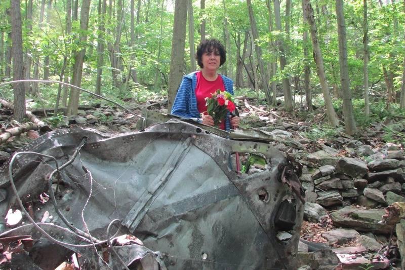 Linda placing flowers near the wreckage of Flight 371.