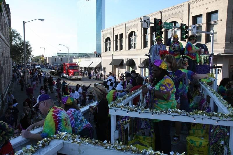 Krewe members ducking street lights during the parade
