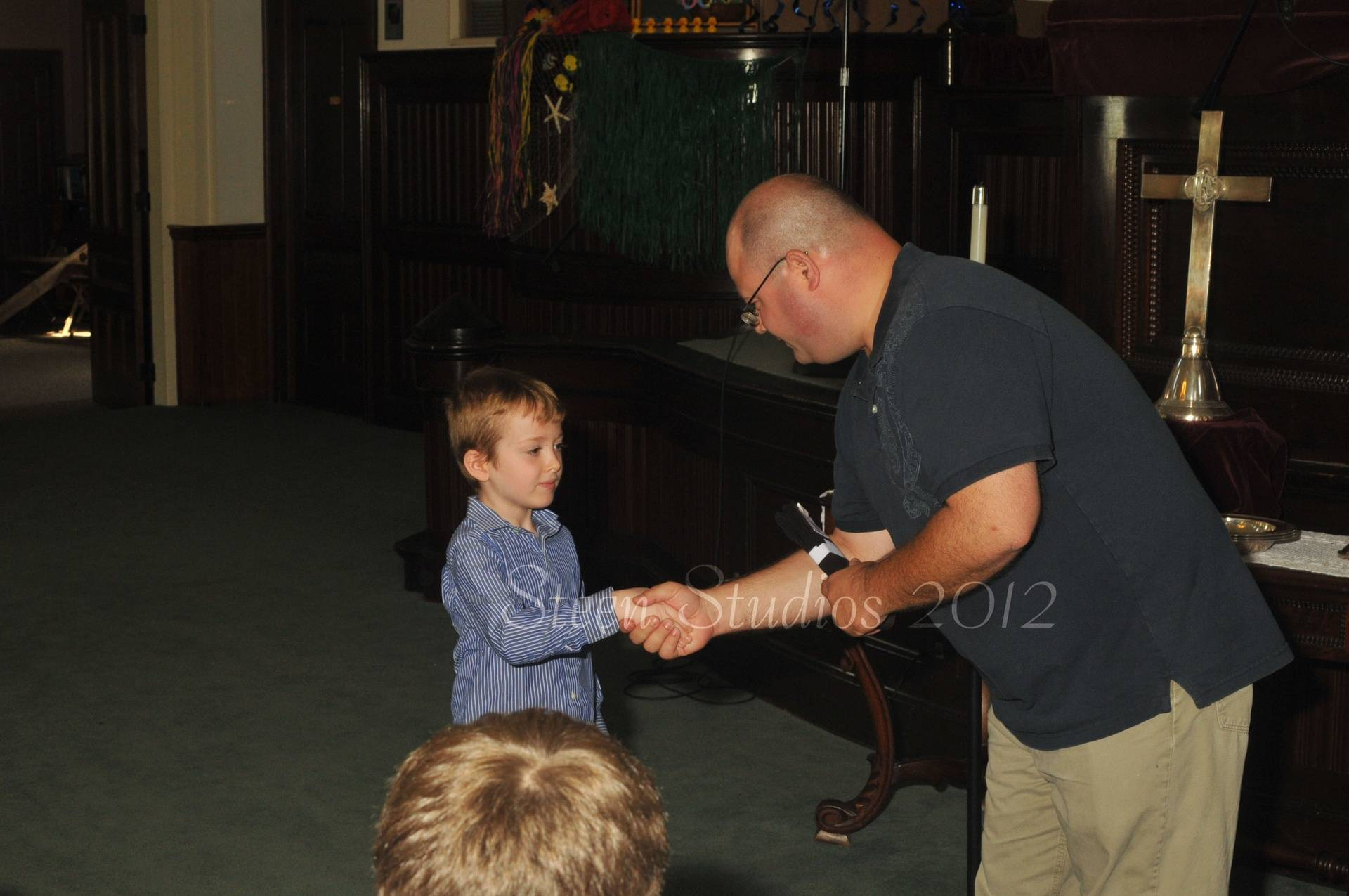 Mr. Q gives Damien his black belt for completing Piano Karate