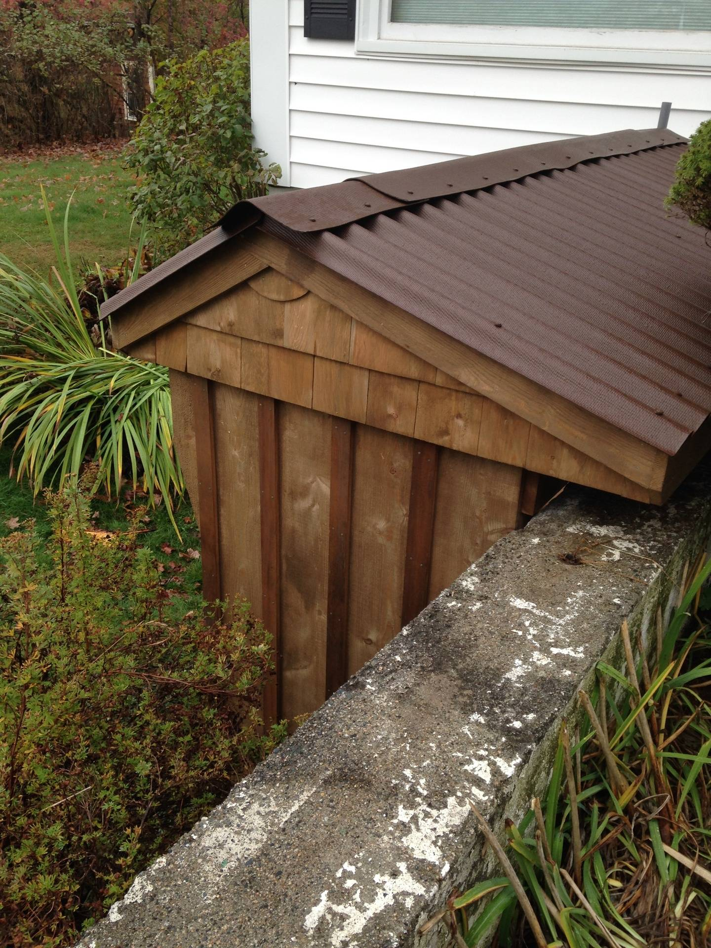 side view of shed custom built for location against large retaining wall