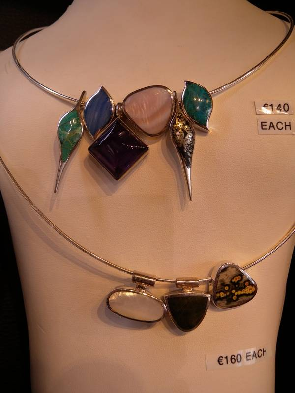 assorted natural stone pendants set in silver on silver cables