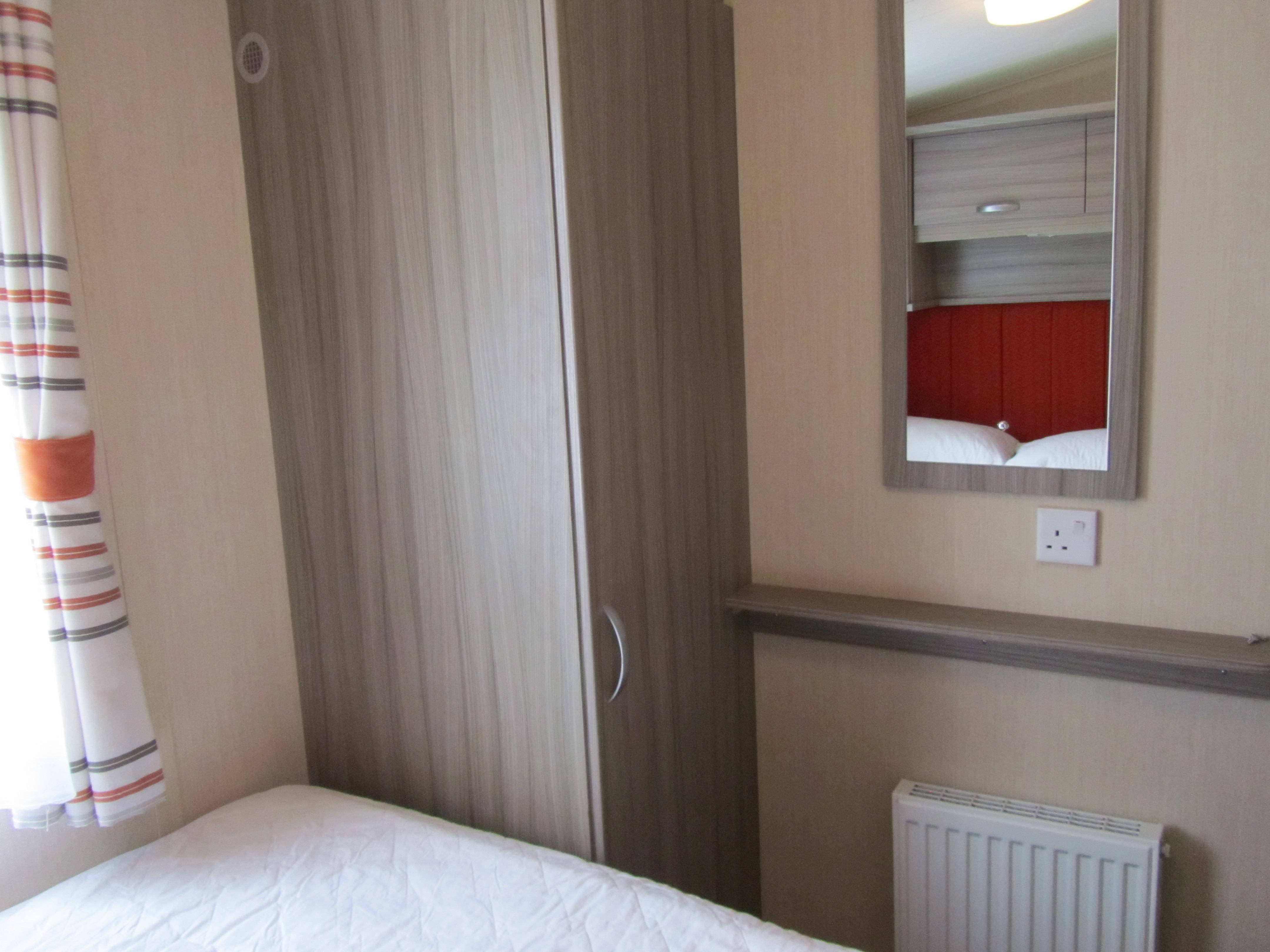 wardrobe in double bedroom with radiator and mirror