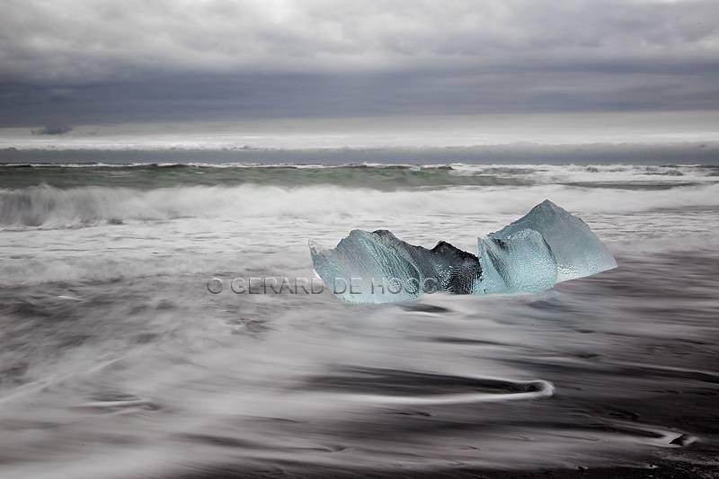 ijs op zwart strand
