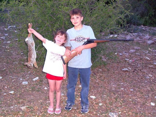 Tyler rabbit hunding with Michaela helping him show off his kill.