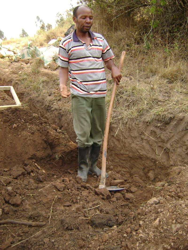 "Gallus, retired water technician, digs out the wall of the trench to hold a concrete and brick box for a ""gate valve"""