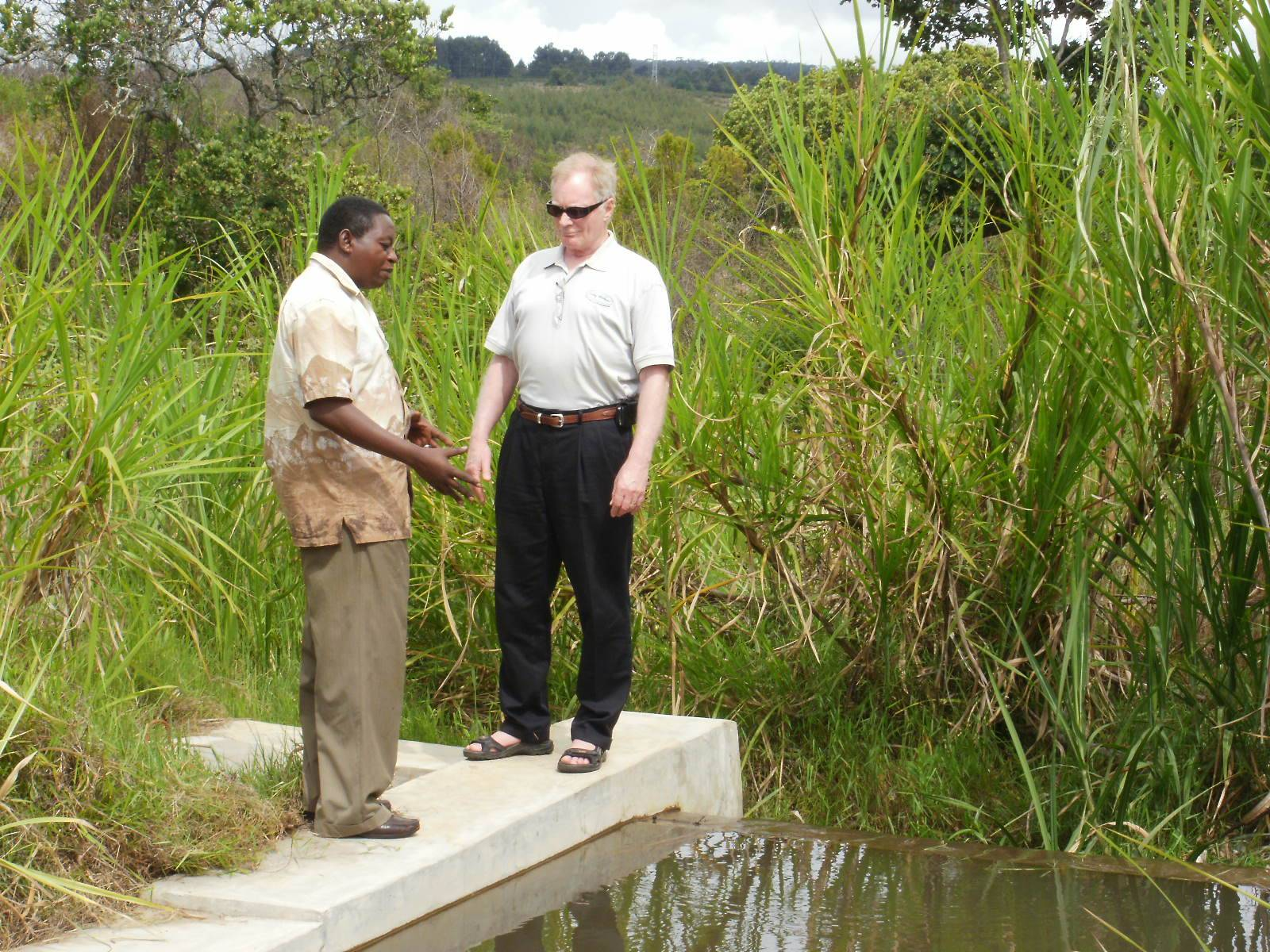 Bud Philbrook, Global Volunteers CEO, visits with Pastor Sagga at the Pommern Water Project intake.