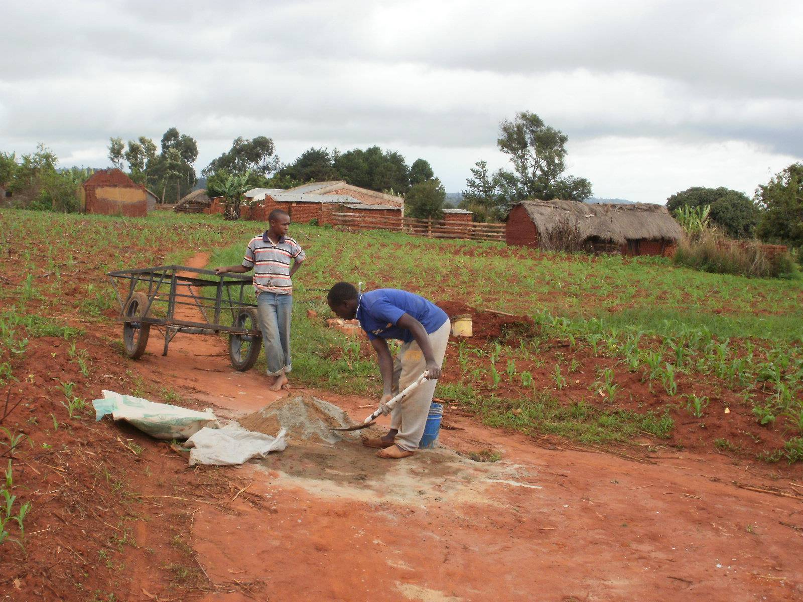 Moses prepares concrete for a water station.