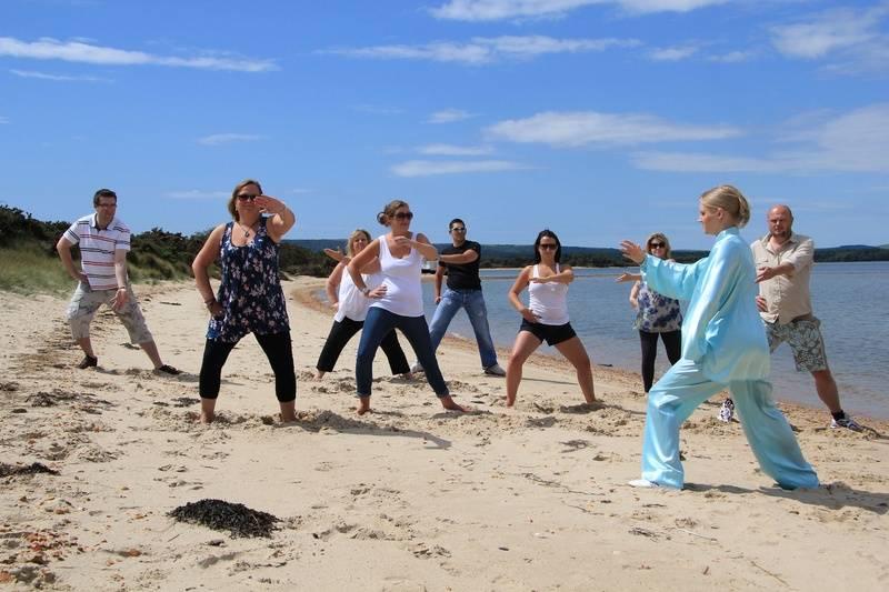 Jakki Lowe teaching a Tai Chi class at the beach