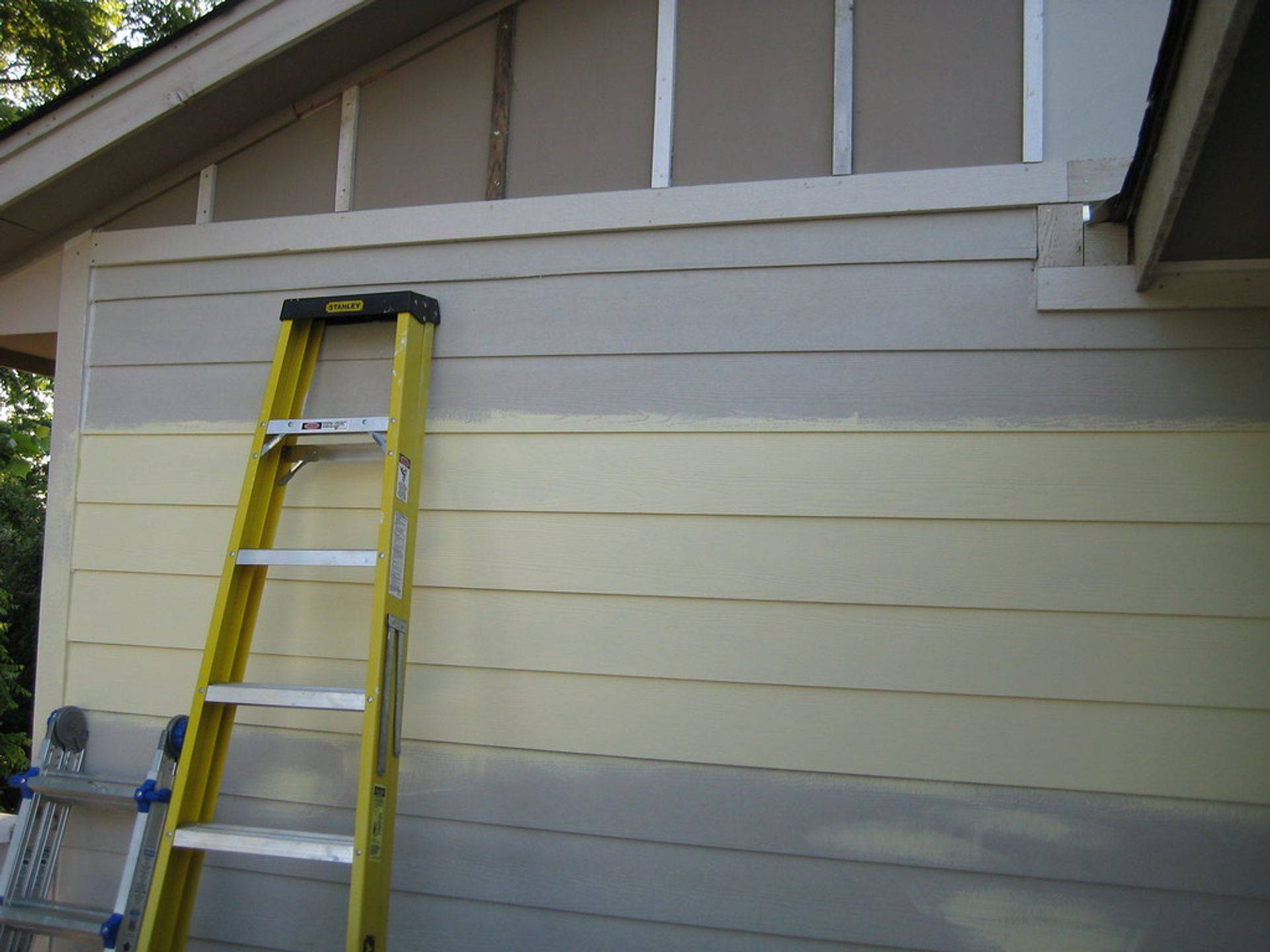 exterior painting being performed on outside of house