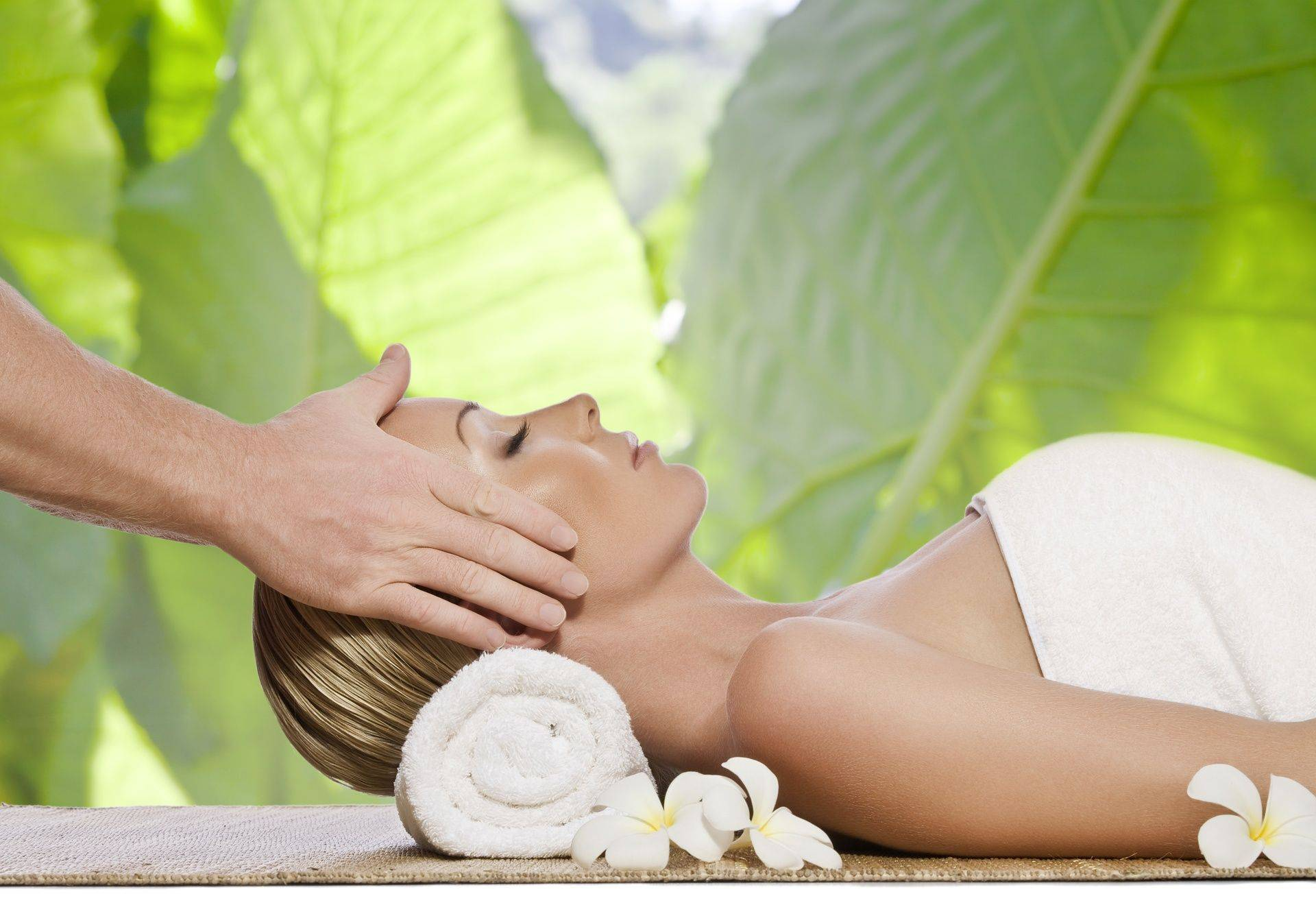 Reiki Treatment lady lying down with hands over her face