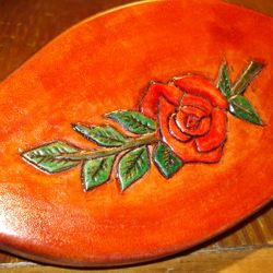 Carved and colored leather backed mirror