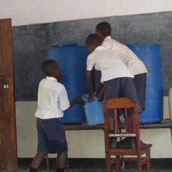 Students are in charge of filling up the water tank in a classroom, so that people can wash their hands.