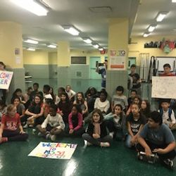 Students pose with signs before a performance by Roger G.