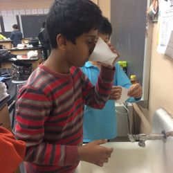 Sidhanth drinks from a paper cup he made.
