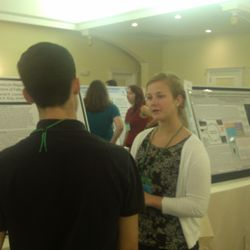 Carly discussing the team's research with an NH-INBRE Conference attendee