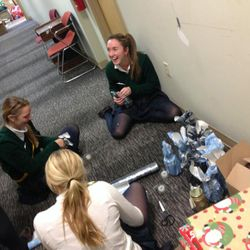 Some students help to wrap the artwork and share a laugh around Christmas time