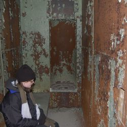 Amanda Lavalley sitting in one of the old holding cells from the police station.