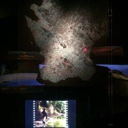 Lite montermiljöer. Karta med ljuspunkter som lyser på inspelningsplatser av filmer som visas på skärmen.
