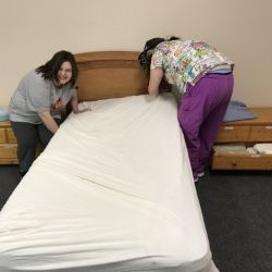 Learning to make a bed properly! Team work!