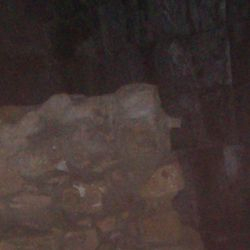 Ghostly figures stand behind the wall, some say they can see a roman with a shield and a hooded figure in fron of him.