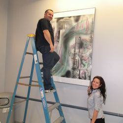 2 volunteers hanging Loren Ellis' mural at 1 of 3 Ryan Chelsea Medical centers in NYC. over now but was a great 5 years.