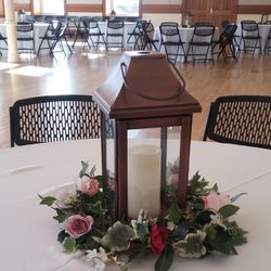 Large dark copper lantern with flicker pillar candle and greenery floral wreath