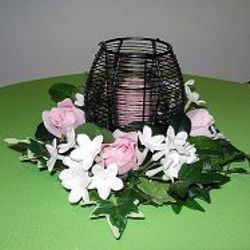 Black wire container with floral wreath and votive candle