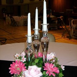 Glass candlesticks with floral wreath and taper candles