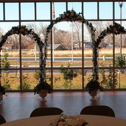 White Wedding Arches main backdrop with added greenery urns