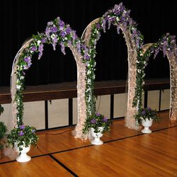 White Wedding Arches backdrop with added greenery urns