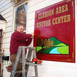Tom Zeller mounting Visitor Center sign at the CCHS Library