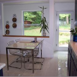 A modern tempered glass table with transparent chairs provide the sensation of a much bigger space. An opening and a window were added to complete the brightness of the kitchen.