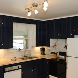 A solid dark navy blue color was chosen for the cabinets and very light colors for backsplash, floor and countertop to oppose the selection of the dark blue color.