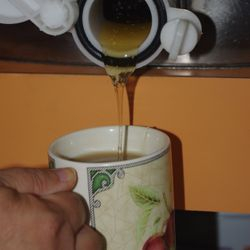 extracting honey into cup of tea